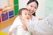 親のお迎えに喜ぶ乳児と笑顔の保育士