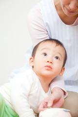 保育士と上を見上げる乳児