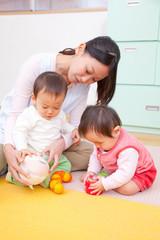 おもちゃで遊ぶ乳児2人と保育士