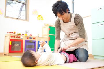 乳児のおむつ替えをする男性保育士
