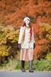 紅葉を眺めながら歩く笑顔の女性