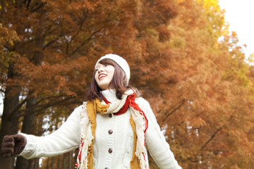 紅葉の並木道を歩く笑顔の女性