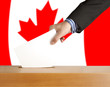Hand with ballot and box on Flag of Canada