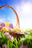 art Easter basket with Easter eggs on spring lawn