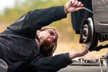 Handsome young man repairing car