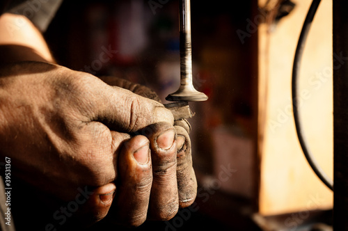 Hands of a worker polishing metal