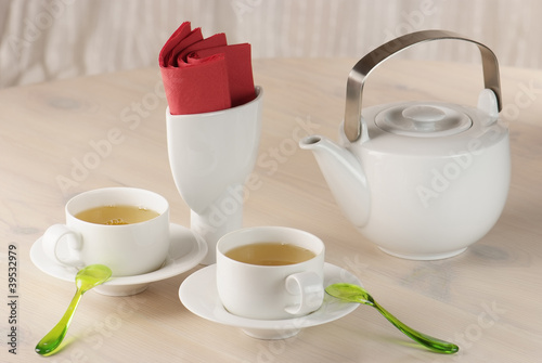 two cups of green tea and teapot on the table