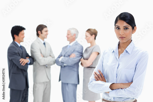 Close-up of a multicultural business team talking and a serious woman in foreground