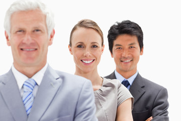 Close-up of two smiling business people behind their boss with focus on the woman