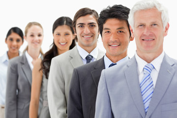 Close-up of smiling business people in a single line with focus on the second person