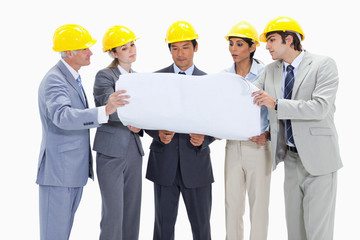 Business people wearing safety helmets looking at something on a map
