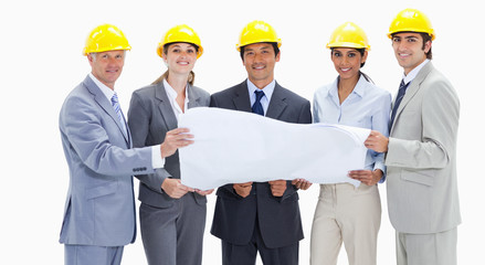 Close-up of smiling business people wearing safety helmets holding a map