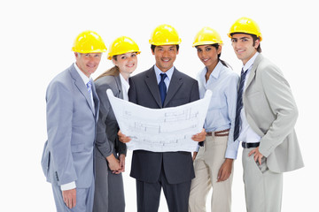 Close-up of smiling business people wearing safety helmets holding construction plans