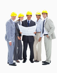 Smiling business people with safety helmets holding construction plans