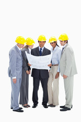 Business people wearing safety helmets watching a construction plan