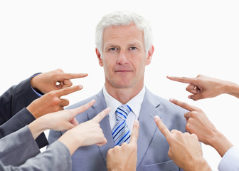 Serious businessman with fingers being pointed at him