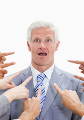 Close-up of shocked businessman with fingers being pointed at him