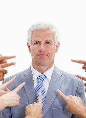 Close-up of serious businessman with fingers being pointed at him