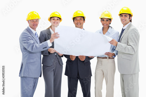 Smiling business people wearing safety helmets holding a map