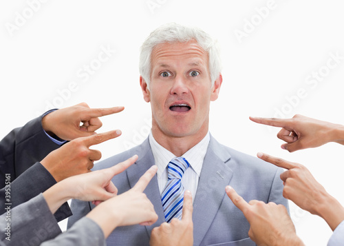 Shocked businessman with fingers being pointed at him