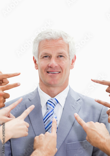 Smiling businessman with fingers being pointed at him