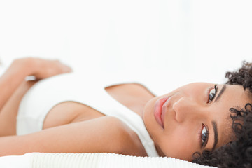 Close-up of a sexy frizzy haired woman lying on her bed