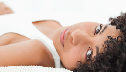 Close-up of a charming frizzy woman lying on her bed