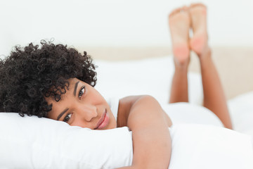 Portrait of a cute  woman lying on her bed