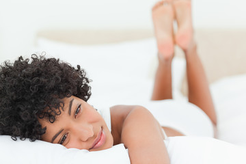 Smiling woman lying on her bed