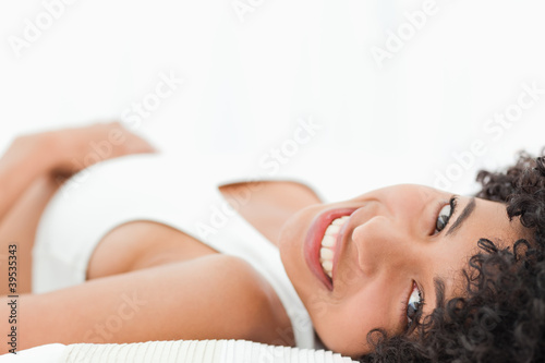 Close-up of a sexy smiling frizzy haired woman lying on her bed