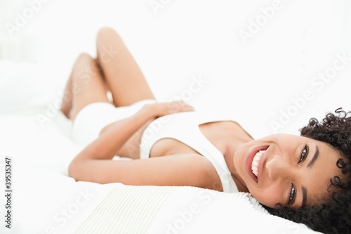 Sexy frizzy haired woman lying on her bed