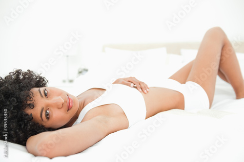Portrait of a sexy frizzy haired woman lying on her bed