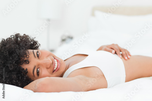 Portrait of a smiling half-breed woman lying on her bed