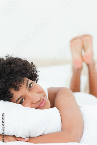 Close-up of a cute woman lying on her bed