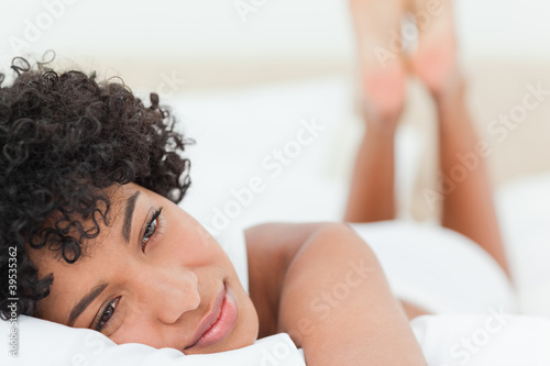Close-up of a smiling woman lying on her bed