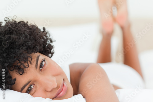 Portrait of a smiling woman lying on the belly