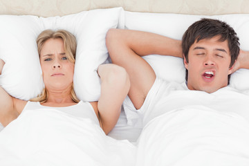 Woman is very angry with the man's snoring and has a pillow over her ears