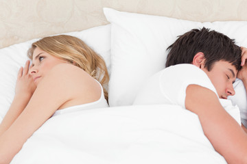 Man and woman sleeping in the bed with their backs to each other