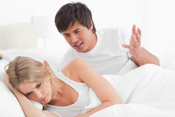 Man and woman arguing in bed, her back turned to him looking angry