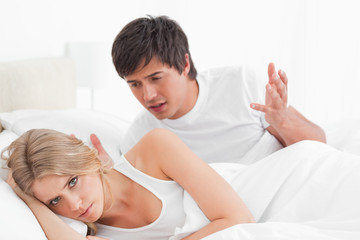 Man and woman arguing in bed, woman looking away from him