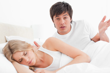 Man in bed looking forward with a confused look as the woman sleeps