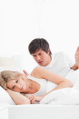 Man and woman in bed, man agruging with woman who is turned away