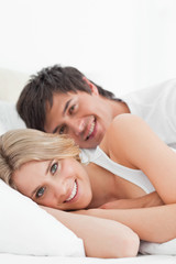 Close up, Man and woman smiling in bed embracing each other and looking forward
