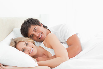 Man and woman holding each other in bed as they smile and look forward