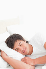 Man in bed smiling softly, with his head on the pillow