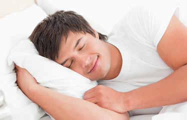 Man with his hand under the pillow smiling softly