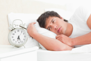 Man in bed waking up not looking happy with his ringing alarm clock