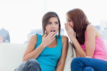 Young woman whispering a surprising secret to a friend