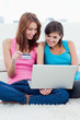Young smiling woman holding a credit card sitting next to a friend with a laptop