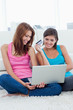 Young woman proudly holding a credit card next to her friend holding a laptop